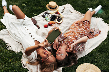 Cool emotional women in stylish midi dresses make funny faces and take selfie outdoors. Charming...