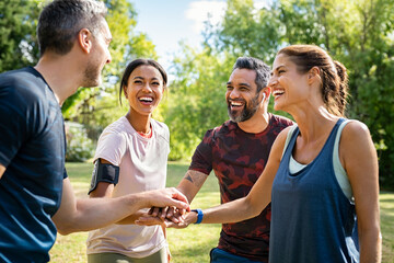 Group of active mature friends in park stacking hands after workout