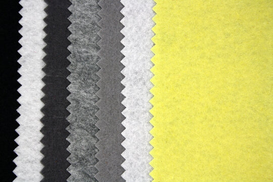 Textile background made of black, grey and yellow felt. Top view.