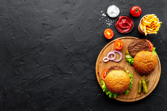 Hamburgers with vegetales and french fries. Top view