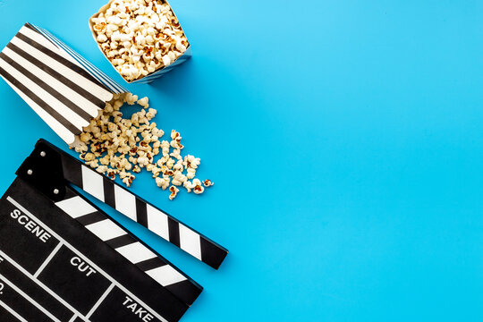 Popcorn with clapperboard and movie film reel. Cinema background