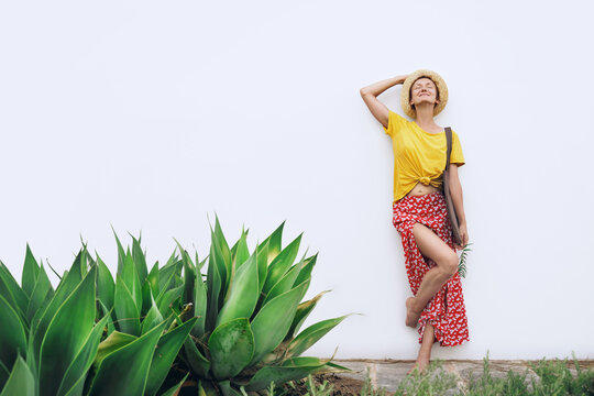Beautiful woman with reusable cotton bag in summer mood. Minimalist style young girl against white wall with green plants. Eco-friendly local production,  slow fashion and caring for ecology concept.
