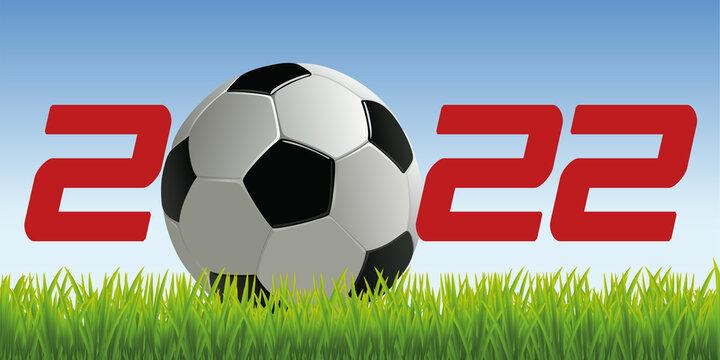 L'année 2022 avec un ballon de football posé sur la pelouse d'un terrain pour symboliser le lancement de la nouvelle saison de compétition.