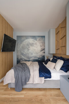 Small and stylish bedroom with moon wall mural