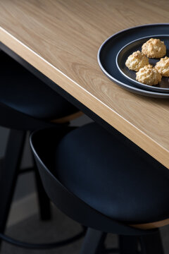 Black chairs under wooden table, close-up