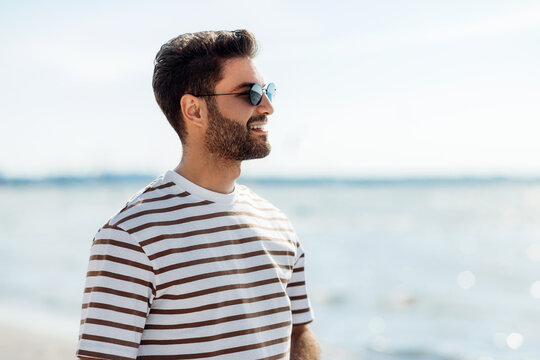 summer holidays and people concept - portrait of happy smiling young man in sunglasses on beach