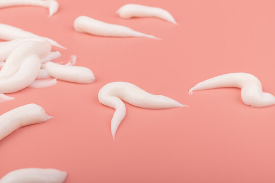 White cosmetic cream smear isolated on pink background. Skincare product creamy texture.