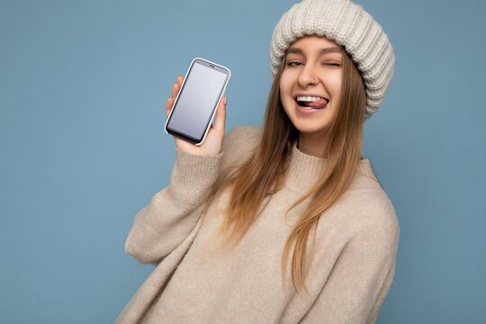 Sexy winking beautiful young woman wearing stylish beige sweater and beige knitted winter hat poising isolated over blue background with empty space holding in hand and showing mobile phone with empty