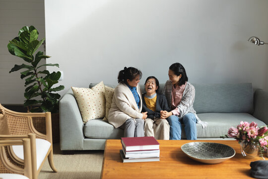 Happy senior asian woman at home with adult daughter and granddaughter embracing