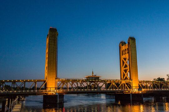Tower Bridge and lights reflected on the Sacramento River. Sacramento and Yolo Counties, California, USA.