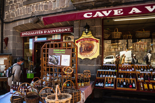 Besse, France - May 30, 2021: Unrecognizable woman in face mask against Covid-19 entering to local food wine specialties shop in medieval town in Auvergne. French tourism during coronavirus pandemic.