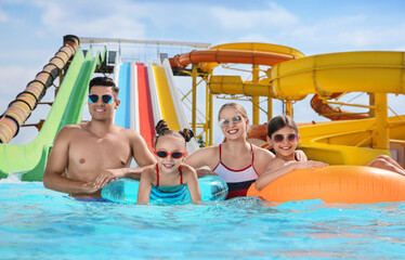 Fototapeta Happy family with inflatable rings in swimming pool at water park obraz