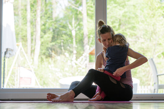 Mother and toddler daughter cuddling on a fitness mat