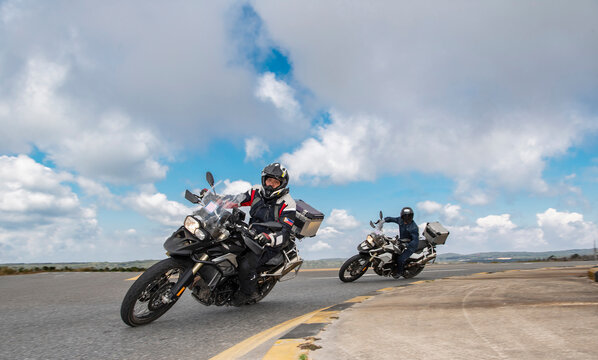 men leaning their adventure motorbikes into turn on road trip