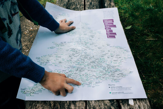 child pointing at a map of England whilst outdoors exploring