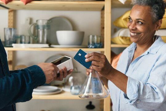 Woman paying for purchase with credit card on tap credit card reader