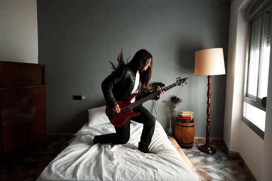 A man with long hair playing bass guitar on the bed