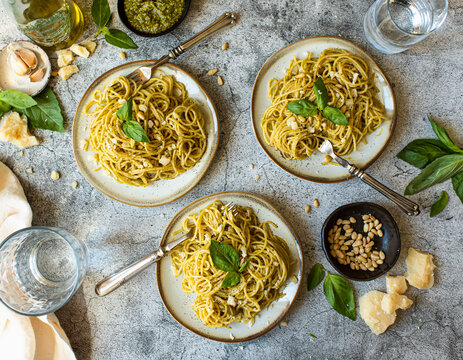 Plates of pesto pasta with it's ingredients on a grey background.