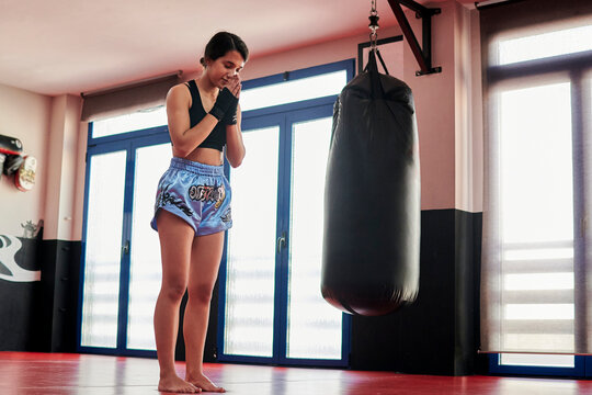 """Woman does a """"Muay Thai"""" salute before performing a training session"""