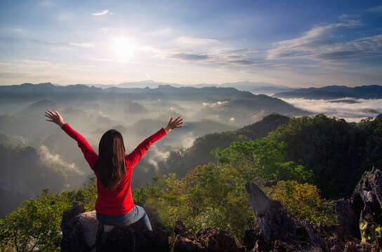 A young women is hike on a clear day. He glad that have successfully climbed the mountain, and admiring nature, and morning mist and the beautiful sun rays, Ban Jabo, Mae Hong Son, Thailand