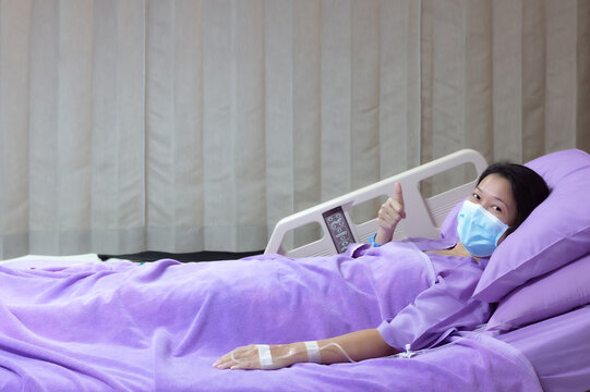 Young Asian female patient is smiling and showing Thumbs up gesture. Patient feels happy and comfortable with treatment and therapy on hospital bed in hospital room. Medical healthcare concept.