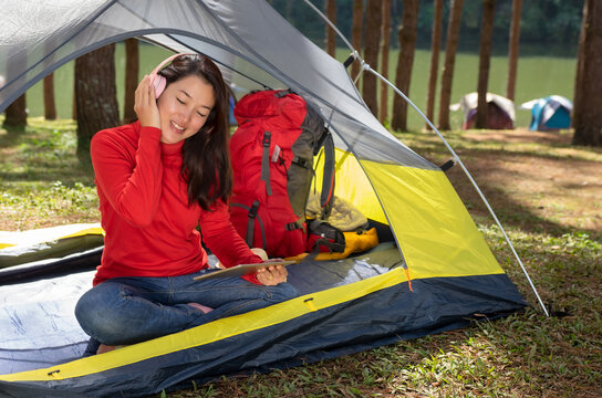 A woman Enjoy listening to music from headphones with play tablet. She sat in a yellow tent. She backpacking camping In the middle of a pine forest beside Lake. Pang Oung, Mae Hong Son, Thailand