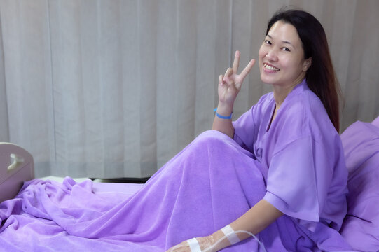 Asian female patient smiling and showing encouragement. Patients feel happy and comfortable when they are treated by hospitalization in the hospital room. Medical health care concept.