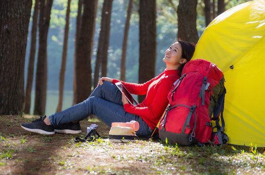 A woman leans against a yellow tent with a red backpack, She is use a tablet and enjoying nature in the midst of a beautiful pine forest beside lake, Pang Oung, Mae Hong Son, Thailand.