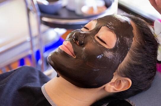 Beautiful asian woman Facial mask with natural mud to nourish the skin for beauty.  Phu Klon, Mae Hong Son Province, Thailand.
