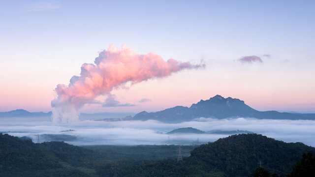 Beautiful sea of fog in the mountains, green forest and steam from the coal-fired power plant in the morning sunrise . Mae moh, Lampang, Thailand