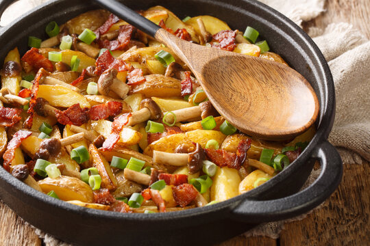 Home-style fried potatoes with green onions, mushrooms and bacon close-up in a frying pan. horizontal