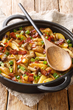 Fried potatoes with bacon and honey fungus mushrooms close-up in a frying pan on the wood background. Vertical