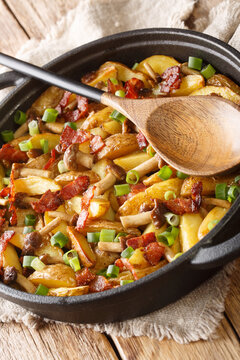 Fried potatoes with bacon and mushrooms close-up in a frying pan on the table. Vertical