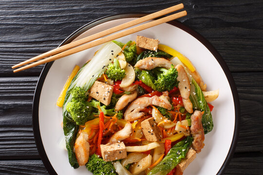 Tasty Stir fry mix of vegetables, chicken and tofu close-up in a plate on the table. Horizontal top view from above