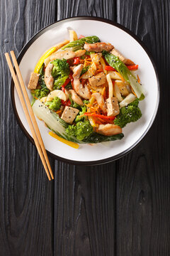 Asian Stir fry pepper,  pak choi, carrots, broccoli, chicken and tofu close-up in a plate on the table. Vertical top view from above