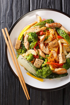 Stir fry vegetables, chicken and tofu close-up in a plate on the table. Vertical top view from above