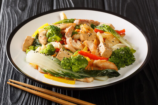 Stir Fried Asian mix of chicken, tofu and seasonal vegetables close-up in a plate on a black wooden background. horizontal