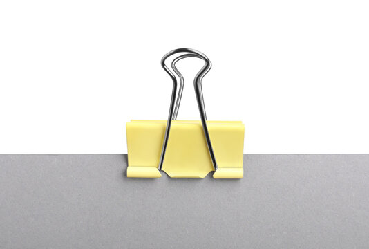 Grey paper with yellow binder clip isolated on white