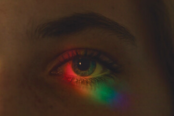 Close up of a blue eye in darkness illuminated with rainbow