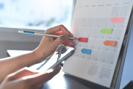 Event planner timetable agenda plan on organize schedule event. Business woman using mobile phone and taking note on calendar desk on office table