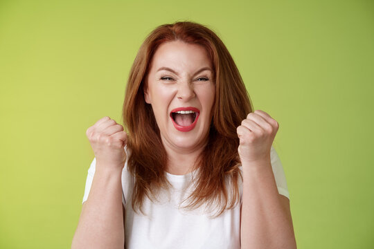 Yeah we did it. Joyful lucky redhead middle-aged female winner pump fists up celebration success gesture yelling triumph joy smiling broadly celebrate awesome news stand green background happy