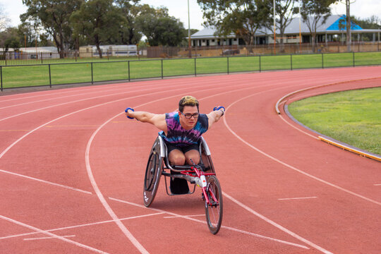 young man in racing wheelchair on athletics track