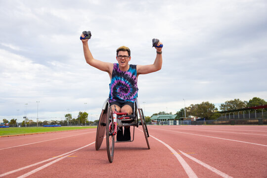 young guy in racing wheelchair celebrating his achievement