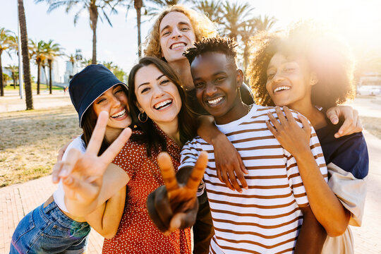 Portrait group of young multicultural trendy friends looking at camera while standing by palm trees background - Outdoor photo of diverse happy people having fun in summer - Focus on black guy