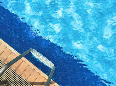 Sunshine and clear water. Top view of swimming pool. Relaxation in summer