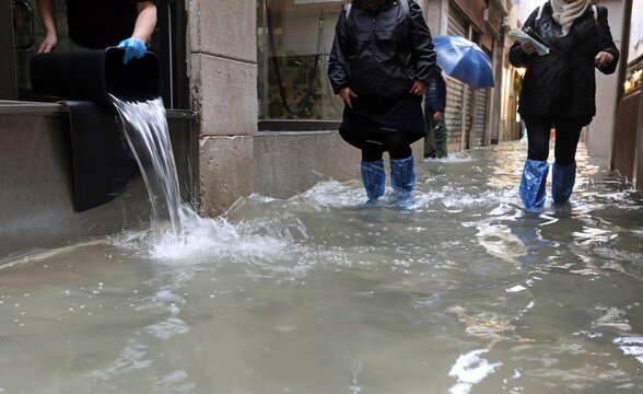 worker empties the water from her shop with a bucket and other people with waterproof gaiters as they walk in the street completely flooded by the high tide in Venice