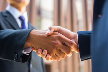 Handshake close-up. Businessman and his colleague are shaking hands in front of modern office...