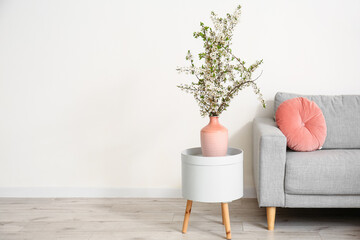 Fototapeta Vase with beautiful blossoming branches on table in stylish interior of room obraz