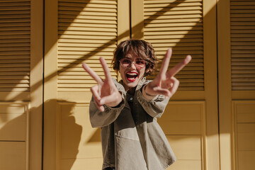 Fototapeta Good-humored woman with red lips showing peace sign on yellow background. Cool lady with curly hair in glasses smiles on bright backdrop.. obraz