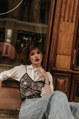 Fototapeta Fashionable lady in jeans with black lace and jeans poses on background of wooden door. Curly girl with bright red lips looks into camera at street.. obraz
